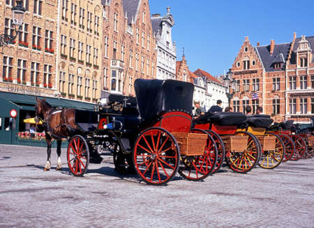 market place: Horse drawn carriages in the Market Place Bruges Belgium Western Europe. Editorial