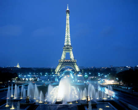 Elevated view of the Eiffel Tower lit up at night with fountains in the foreground Paris France Western Europe. Editorial