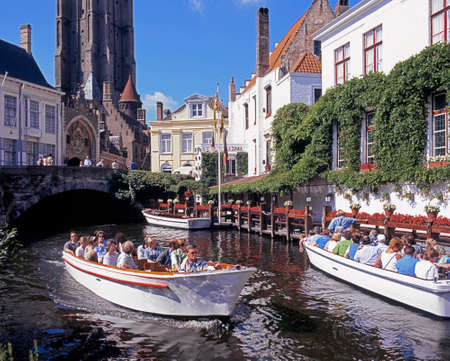 western europe: View along the Dijver with tourists taking boat trips in the foreground Bruges Belgium Western Europe. Editorial