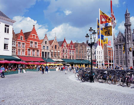 market place: Cycles and pavement cafes in the Market Place Bruges Belgium Western Europe.