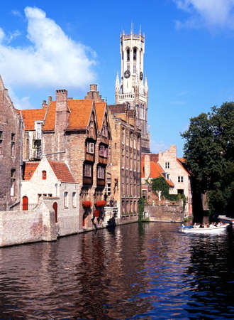 western europe: The Belfry seen from Rozenhoedkaai with tourists taking a boat ride Bruges Belgium Western Europe. Editorial