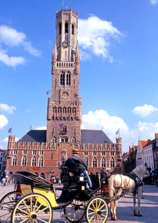 market place: The Belfry in the Market Place with a horse and carriage in the foreground Bruges Belgium Western Europe.