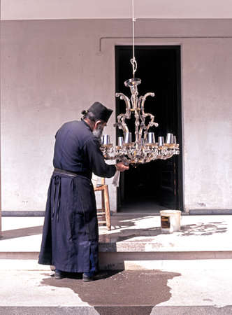ceiling light: Monk cleaning a ceiling light at the Kykkos Monastery the most powerful in Cyprus and in Greek Orthodox Church Cyprus. Editorial