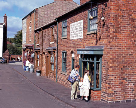 country living: People looking at Victorian shops along the main village shopping street at the Black Country Living Museum Dudley West Midlands England UK Western Europe.