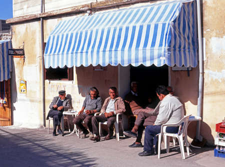 cypriot: Cypriot men sitting outside a bar in the village centre Neo Chorio Cyprus.