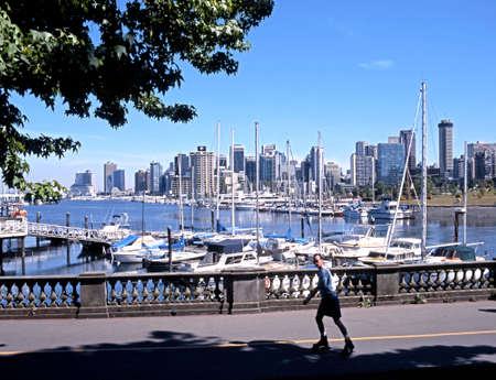 british man: Man skating along the Stanley Park Promenade with downtown skyscrapers to the rear Vancouver British Columbia Canada.