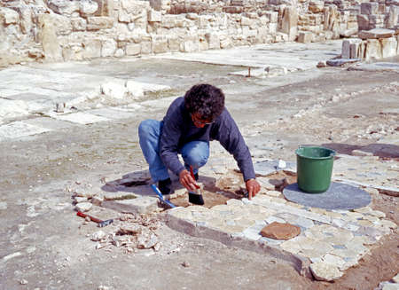 restoring: Archaeologist restoring floor of the Basilica Kourion Near Limassol Cyprus.