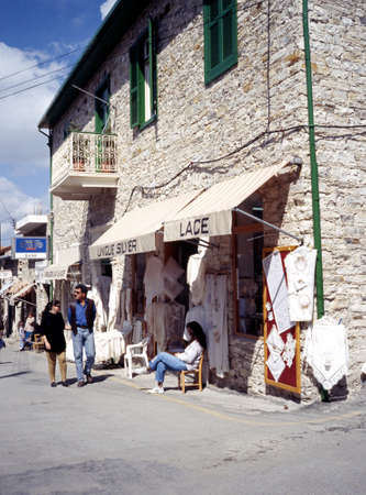 Couple walking past a lace shop in the town centre Pano Lefkara Cyprus.