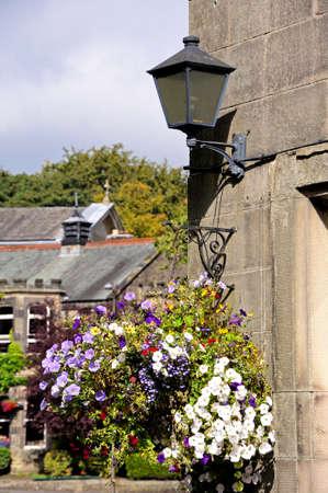 hanging basket: Hanging basket and wrought iron lantern on a stone wall, Buxton, Derbyshire, England, UK, Western Europe. Stock Photo