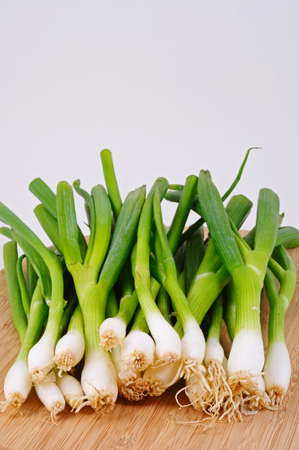 spring onions: Bunch of white spring onions on a wooden chopping board.