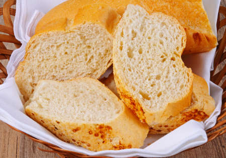 crusty: Crusty French stick cut into pieces in a bread basket. Stock Photo