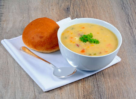 haddock: Fish chowder soup including smoked haddock cod salmon and vegetables served with a bread roll. Stock Photo