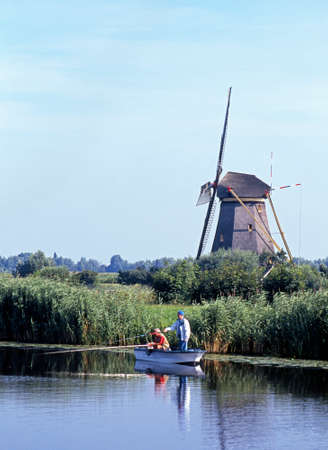 dyke: Two local men fishing on the dyke wind a windmill to the rear, Kinderdijk, Holland, Netherlands, Europe. Editorial