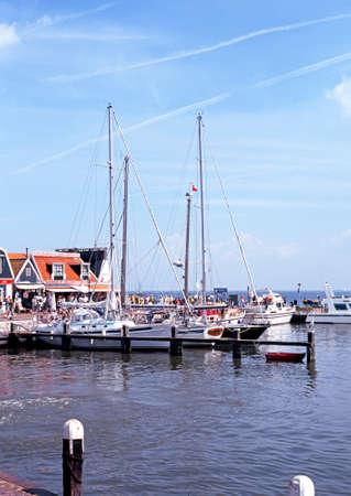 volendam: Yachts moored in the harbour with pavement cafes to the rear, Volendam, Holland, Netherlands, Europe.