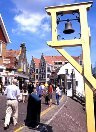 volendam: Bell on harbour wall with tourists walking along the shopping street, Volendam, Holland, Netherlands, Europe.