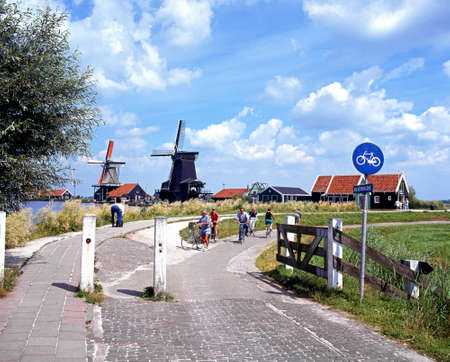 zaan: Row of windmills along the banks of the river Zaan with a cyclists in the foreground, Zaanse Schans, Holland, Netherlands, Europe. Editorial