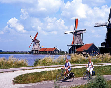 zaan: Row of windmills along the banks of the river Zaan with a couple cycling in the foreground, Zaanse Schans, Holland, Netherlands, Europe.