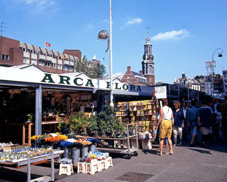 Tourists walking around the market with the flower market in the foreground, Amsterdam, Holland, Netherlands, Europe.