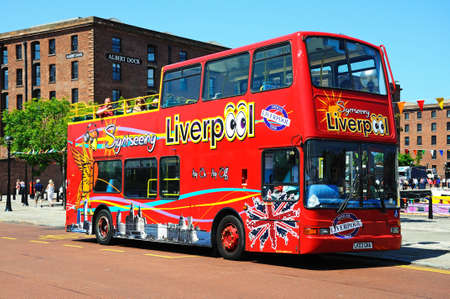 open topped: Red tour bus carrying tourists outside Albert Dock