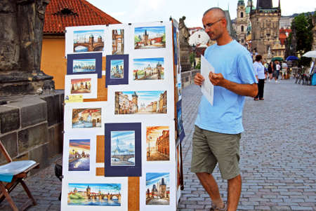 Tourist looking at water colour paintings on Charles Bridge, Prague, Czech Republic, Eastern Europe. Editorial