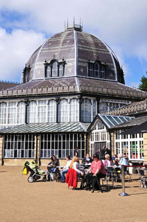 derbyshire: Octagon Hall in the Pavilion Gardens with a pavement cafe in the foreground, Buxton, Derbyshire, England, UK, Western Europe.