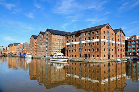 western europe: Boats moored in Gloucester Docks with warehouses to the rear, Gloucester, Gloucestershire, England, UK, Western Europe.