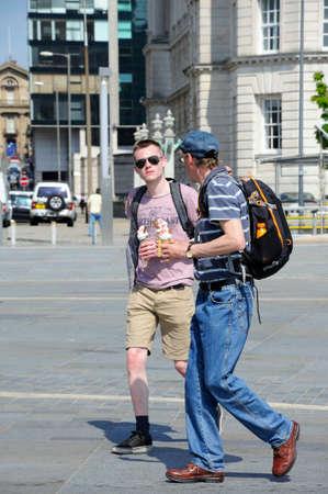 merseyside: Two young backpackers walking along with ice creams, Liverpool, Merseyside, England, UK, Western Europe. Editorial