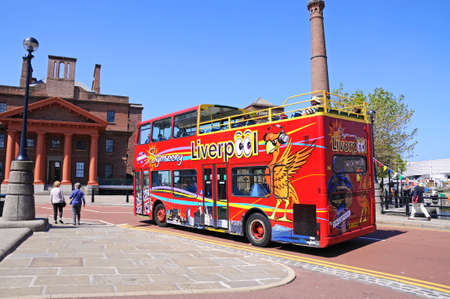open topped: Red tour bus carrying passengers by Albert Dock, Liverpool, Merseyside, England, UK, Western Europe. Editorial