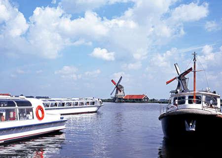 zaan: Pleasure cruisers on the River Zaan with windmill to rear, Zaanse Schans, Holland, Netherlands, Europe. Editorial