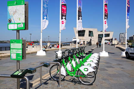 mersey: Row of city hire bikes for rent along the waterfront at Pier Head with the Mersey Ferries building to the rear, Liverpool, Merseyside, England, UK, Western Europe. Editorial