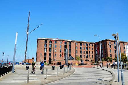 merseyside: Ships mast and cyclists along Albert Dock waterfront, Liverpool, Merseyside, England, UK, Western Europe.