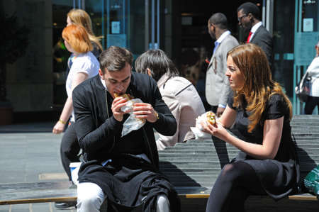 merseyside: Couple sitting on a bench having a takeaway lunch along Whitechapel shoping street in the city centre, Liverpool, Merseyside, England, UK, Western Europe.