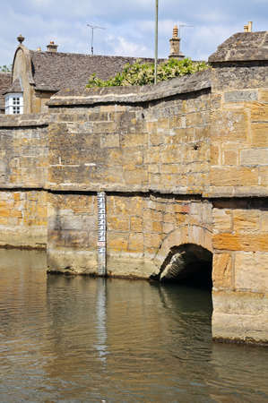 depth gauge: Medieval stone bridge over the river Windrush showing the depth marker, Burford, Oxfordshire, England, UK, Western Europe.
