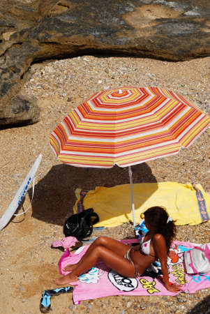 Pretty young woman under parasol on La Caleta beach, Cadiz, Cadiz Province, Andalusia, Spain, Western Europe.