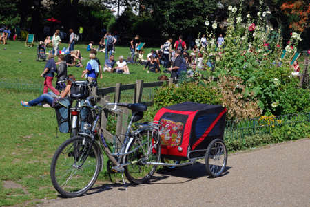 west sussex: Bicycle with child carrying trailer alongside a park, Brighton, West Sussex, England, UK, Western Europe. Editorial