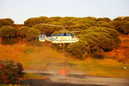 fires artificial: Kamov Ka-32A11BC helicopter registration EC-JSQ collecting water for fire fighting from a golf course lake, Cabopino Golf, Costa del Sol, Malaga Province, Andalucia, Spain, Western Europe.