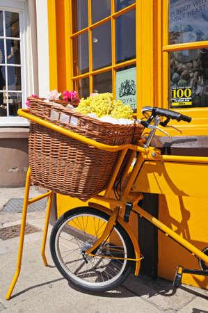 grocers: Bike with wicker basket full of flowers along Bridge Street, Stratford-Upon-Avon, Warwickshire, England, UK, Western Europe. Editorial
