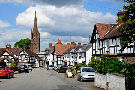 timbered: View along Broad Street with its white timbered buildings and St Peter and St Paul church spire to the rear, Weobley, Herefordshire, England, UK, Western Europe.