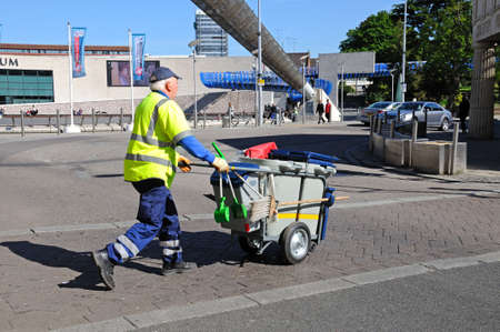 midlands: Rubbish collector pushing his trolley along the pavement at Millennium Place, Coventry, West Midlands, England, UK, Western Europe. Editorial