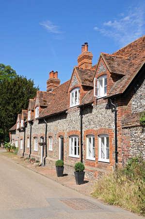 flint: Pretty brick and flint cottages with dormer windows along a village street, Hambledon, Oxfordshire, England, UK, Western Europe.