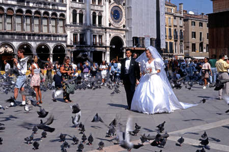 st mark's square: Bride and groom walking through a crowded St Marks Square, Venice, Veneto, Italy, Europe.