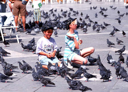 st marks square: Children feeding pigeons in St Marks Square, Venice, Veneto, Italy, Europe. Editorial