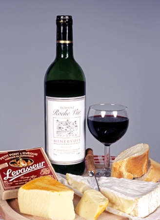 vue: French Minervois Red wine with a selection of French Cheeses and crusty bread, France. Editorial