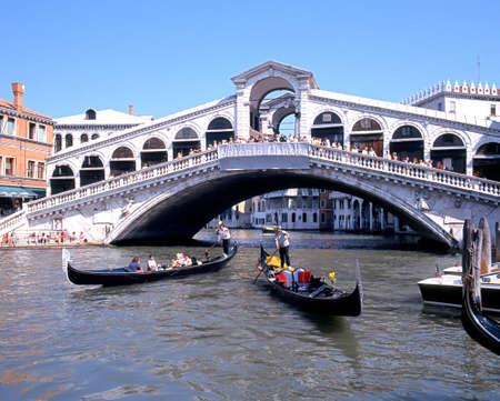 rialto bridge: Tourists taking a Gondola trip along the Grand Canal by the Rialto Bridge, Venice, Veneto, Italy, Europe.