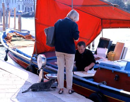 Murano: Fish seller on a boat in the Venetian Lagoon on Murano Island, Venice, Veneto, Italy, Europe.