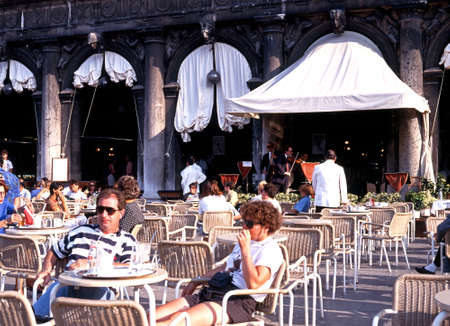 st mark's square: Tourists at a pavement cafe with musicians to the rear in St Marks Square, Venice, Veneto, Italy, Europe.