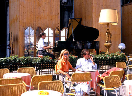 pianista: Pareja sentada en la terraza de un caf� con un pianista tocando en la plaza San Marco, Venecia, V�neto, Italia, Europa.