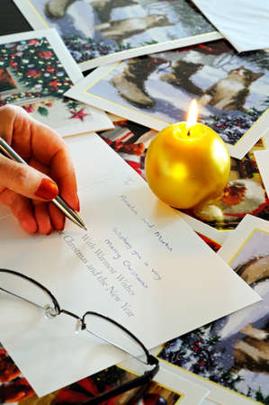 candlelit: Writing Christmas cards by candlelight with cards scattered on the table. Editorial
