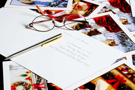 writing western: Scattered Christmas cards with glasses and a pen.