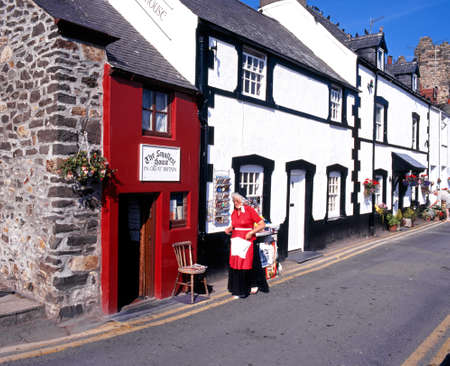 smallest: The Smallest House in Great Britain with a Welsh lady in traditional dress in the foreground, Conwy, Gwynedd, Wales, UK, Western Europe.